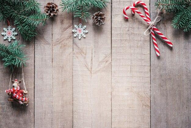モミの木の枝、クリスマスライト、サンタの帽子とスカーフのミニトナカイの図とクリスマスの背景