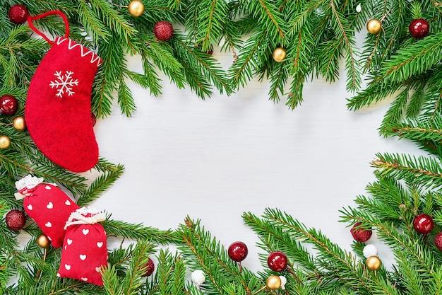 モミの木の枝、クリスマスの靴下とギフトとクリスマスの背景。 tiopビュー、コピースペース。グリーティングカード。