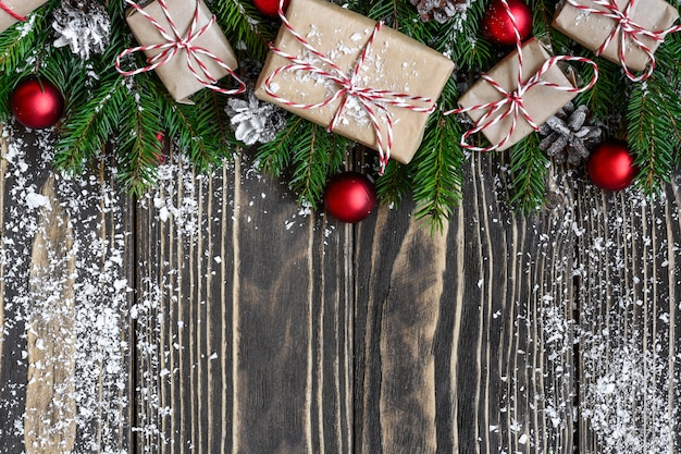 Новогодний фон с еловыми ветками, подарочными коробками, украшениями и сосновыми шишками в снежной рамке