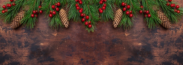 Christmas background with fir tree branches and holly. view from above. horizontal banner. copyspace