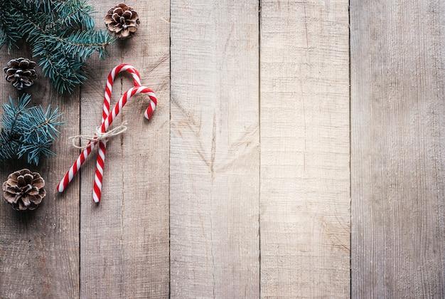 モミの木の枝、松ぼっくり、コピースペースのあるキャンディケインのクリスマスの背景