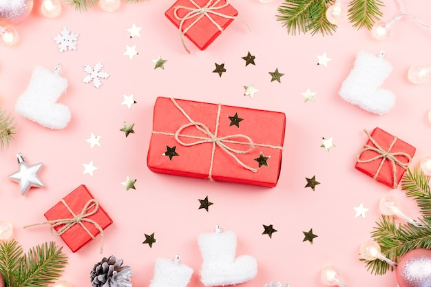 Christmas background with fir tree branches, red giftboxes, decorations, hot drink with marshmallows on pink. copy space