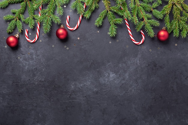 어두운 돌 배경에 전나무, 사탕 지팡이, 빨간 공이 있는 크리스마스 배경. 상위 뷰 복사 공간 - 이미지
