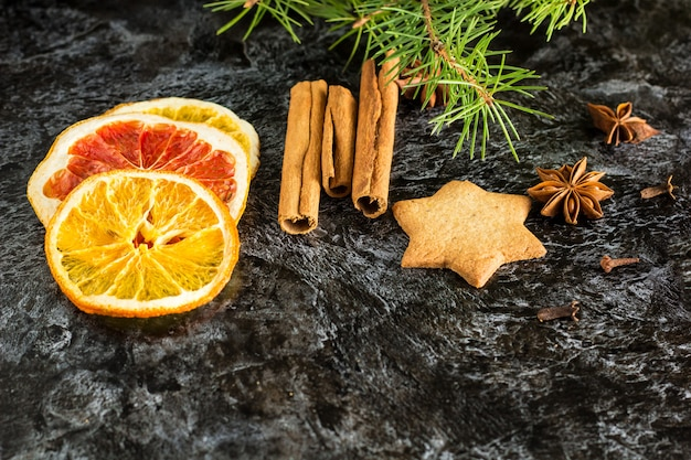 Christmas background with fir tree dry orange cinnamon anise and star of gingerbread cookies on dark background.
