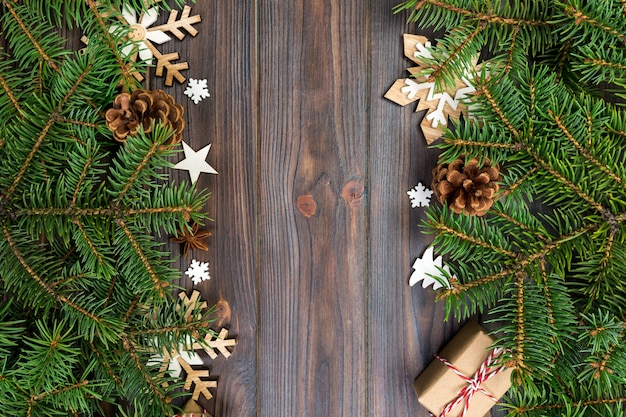 Christmas background with fir tree and gift box on wooden table. top view with copy space for your design.