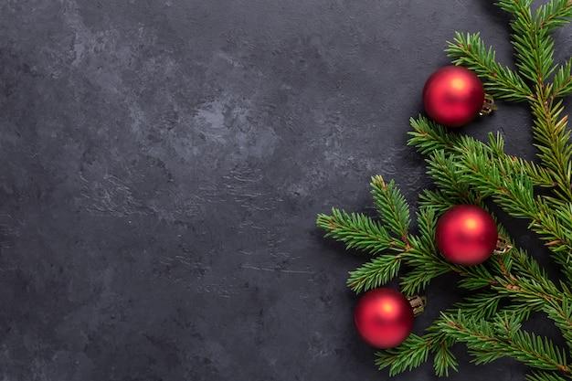 어두운 돌 배경에 전나무, 홀리, 빨간 공이 있는 크리스마스 배경. 상위 뷰 복사 공간 - 이미지