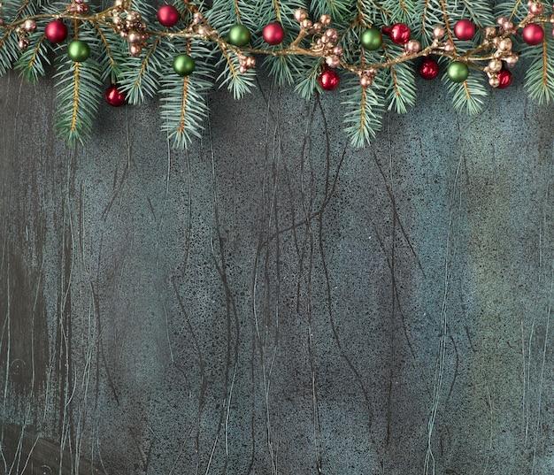 Рождественский фон с еловыми ветками, красными и зелеными шарами и бронзовой гирляндой на темном, копией пространства