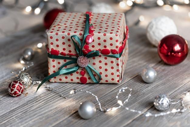 Sfondo di natale con confezione regalo, palline sull'albero e luci bokeh.
