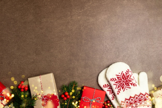 Christmas background with gift box, christmas tree, lights, mittens and decorations