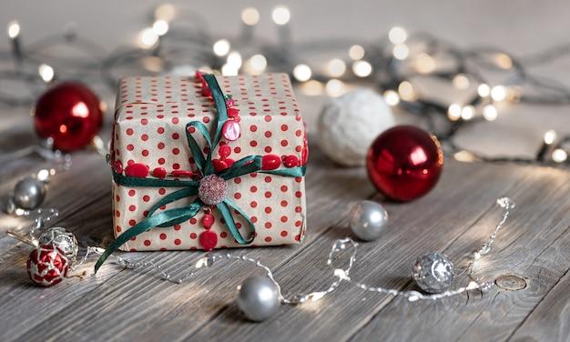 Sfondo di natale con confezione regalo da vicino su superficie in legno, palle di natale e luci bokeh, spazio copia.