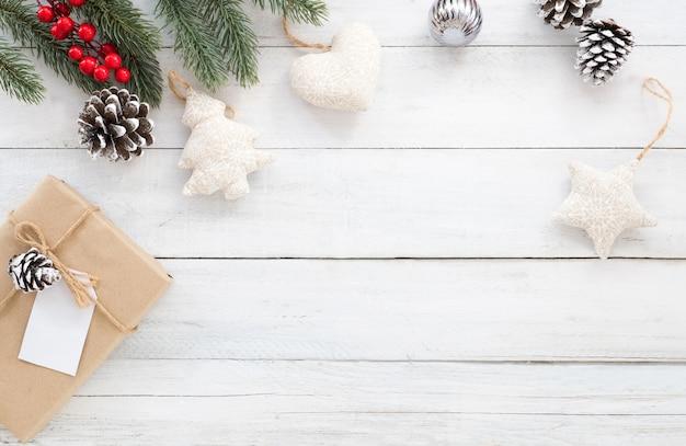 Рождественские фон с подарочной коробке, сосновые шишки, елочные листья, холли берри и украшения деревенском элементы на белом деревянный фон. творческая квартира, вид сверху