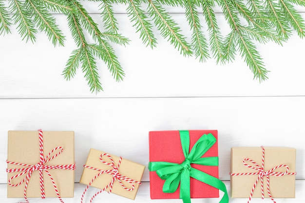 Christmas background with gift boxes and branches of christmas tree on wooden surface
