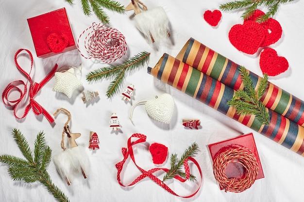 ギフトボックス、リボン、より糸、ロール紙、ニットの心とクリスマスの飾りとクリスマスの背景。冬休みの準備。上面図、フラットレイ