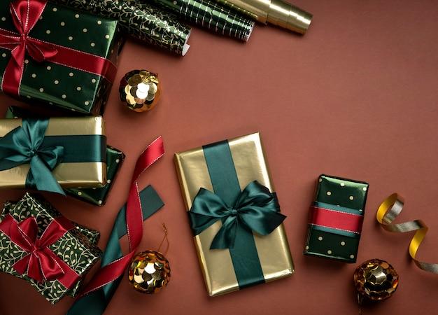 茶色の背景にギフトボックスサテンリボンと包装紙のロールとクリスマスの背景