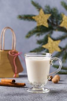クリスマスの背景、ギフトボックス、星、お祭りの装飾、モミの木、シナモンスティック、熱いエッグノッグドリンク。