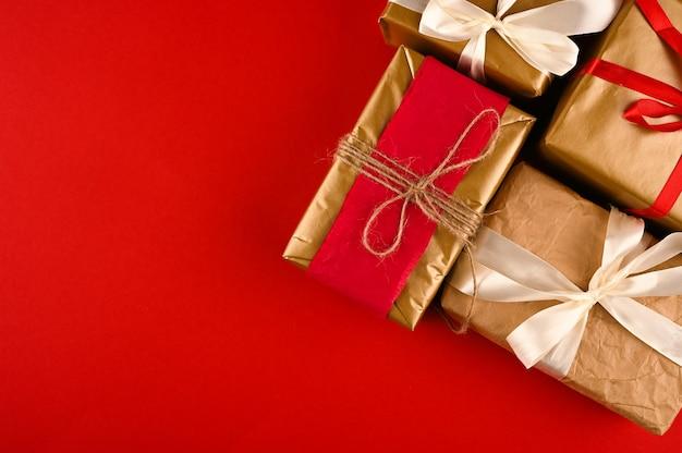 Новогодний фон с подарочными коробками, завернутыми в крафт-бумагу над красным столом.