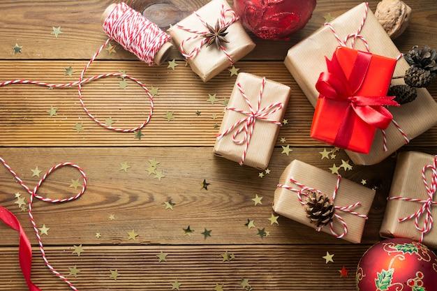 ギフト用の箱とクリスマスの背景は、お祝いのホリデーシーズンを祝うために準備された木製のテーブルの上にペーパークラフトで包まれました。コピースペース。