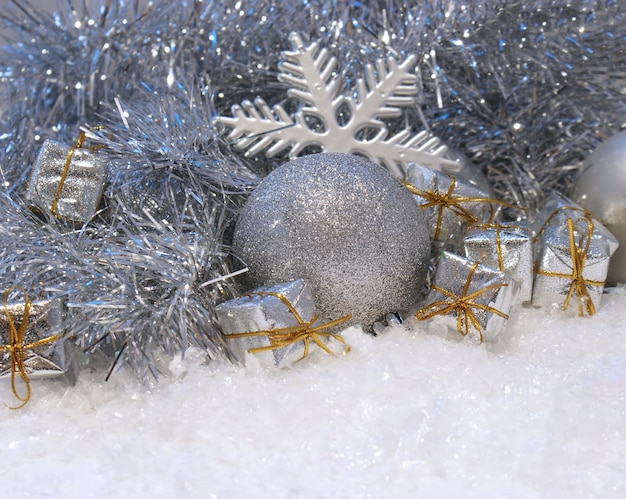 Christmas background with gifts and baubles nestled in snow
