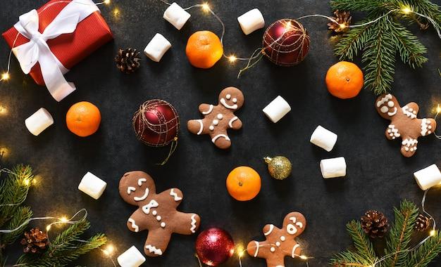 진저 쿠키와 선물 크리스마스 배경입니다. 검정색 배경에 새 해의 레이아웃.