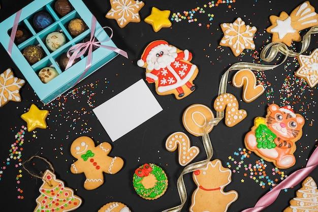 灰色の表面の休日の気分カードの上面図のコピースペースにジンジャーブレッドとクリスマスの背景