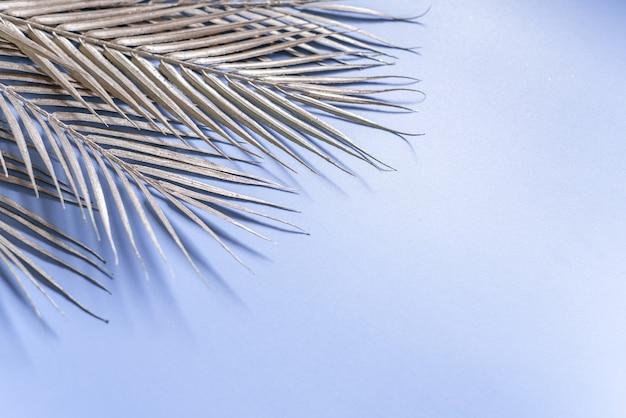 キラキラシルバーのヤシの葉と青い背景、冬のクリスマスや新年の創造的なレイアウトとクリスマスの背景