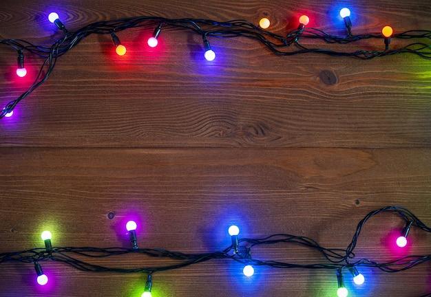 Новогодний фон со светящимися гирляндами на деревянной поверхности
