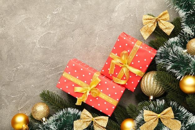 Новогодний фон с золотыми украшениями и подарочной коробкой на сером бетонном фоне. вид сверху.