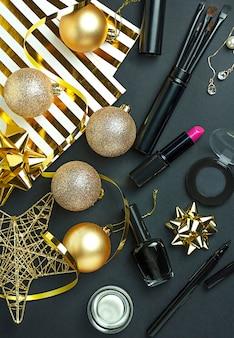 Новогодний фон с золотыми шарами, змеевиком и женской косметикой. новогодняя открытка.