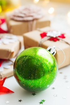 Christmas background with green decorative ball, presents and decorations for christmas tree.