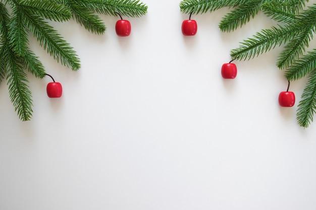 Новогодний фон с зелеными еловыми ветками и маленькими красными игрушками