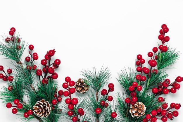 Новогодний фон с зелеными ветвями ели, сосновыми шишками и красными ягодами на белом фоне.
