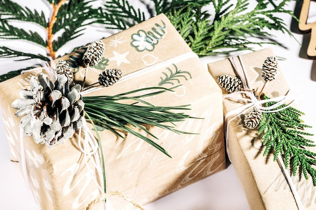 Christmas background with handicraft gift boxes clews of rope and decorations with pine cones