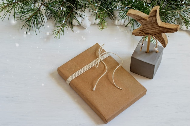 Christmas background with handmade gift wrapped in brown craft paper and knot tied.