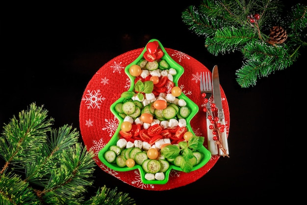 Christmas background with healthy salad on christmas tree shape plate and fir branches top view