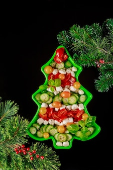 Christmas background with healthy salad on christmas tree shape plate and fir branches. top view.