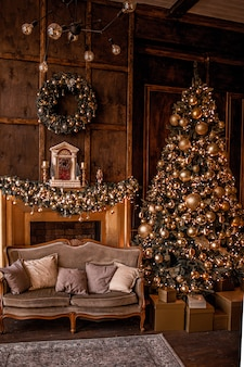 Christmas background with illuminated fir tree with golden decpration and fireplace in living room. cozy holiday home