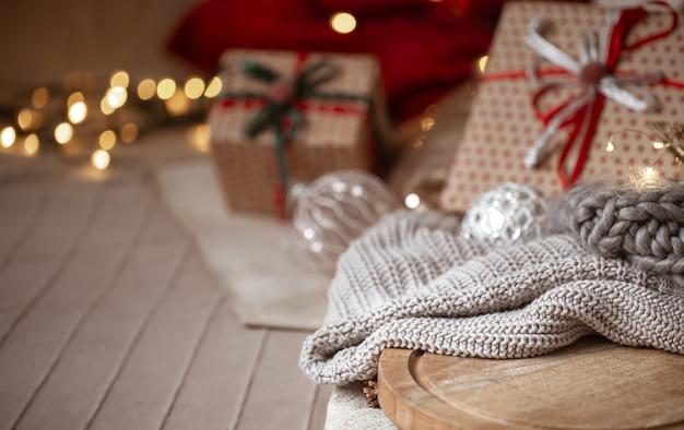 Новогодний фон с вязанным свитером в фокусе на размытом фоне рождественских украшений и обернутых подарков копирует пространство.