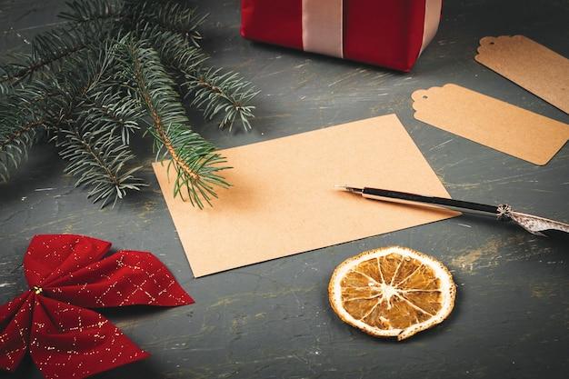 계절 장식으로 둘러싸인 편지 봉투와 깃털 펜이 있는 크리스마스 배경