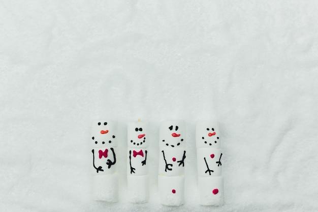 偽の雪の上のマシュマロ雪だるまとクリスマスの背景。高品質の写真