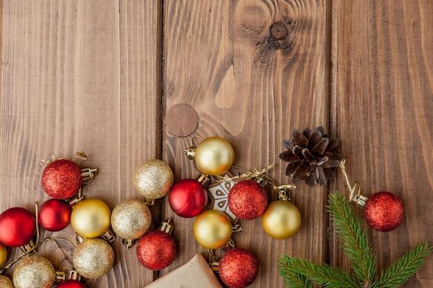 Новогодний фон с новогодними игрушками и еловой веткой на деревянном столе.