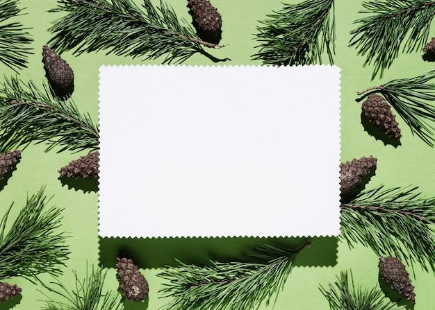緑のメモ用紙とクリスマスの背景。松の枝や円錐形の装飾