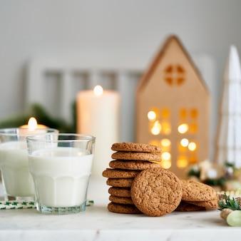 오트밀 생강 칩 쿠키가 있는 크리스마스 배경 주방에서 아늑한 저녁 우유 두 잔