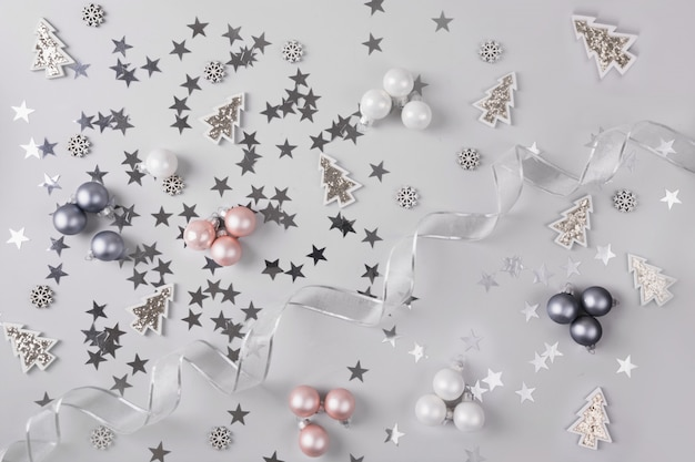 Christmas background with pastel grey pink glitter balls , stars, on silver grey. top view. xmas pattern. new year.