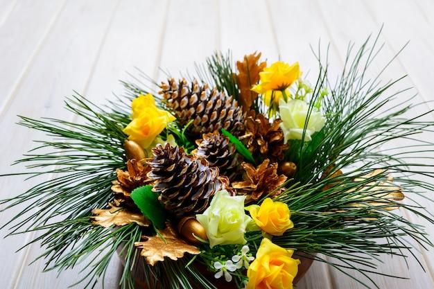 Рождественский фон с сосновыми ветками и золотыми украшенными еловыми шишками