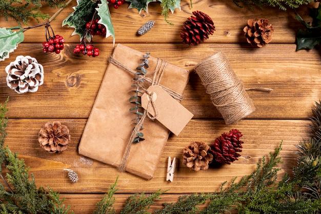 Рождественский фон с подарком и сосновые шишки