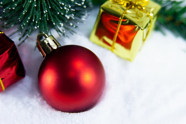 Christmas background with a red ball and , golden gift in snow
