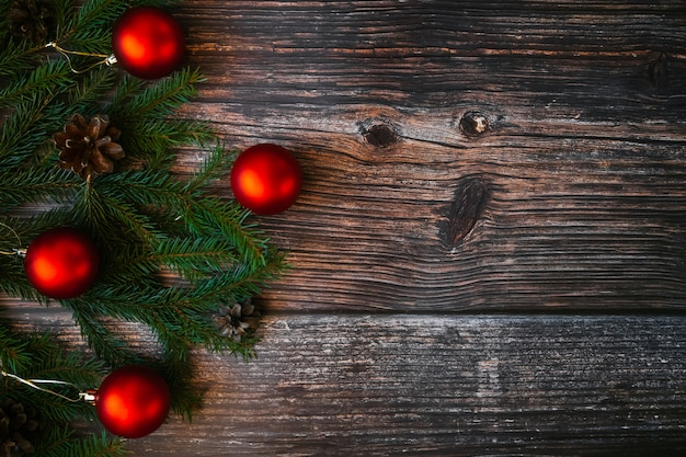 Christmas background with red balls, fir branches and pine cones