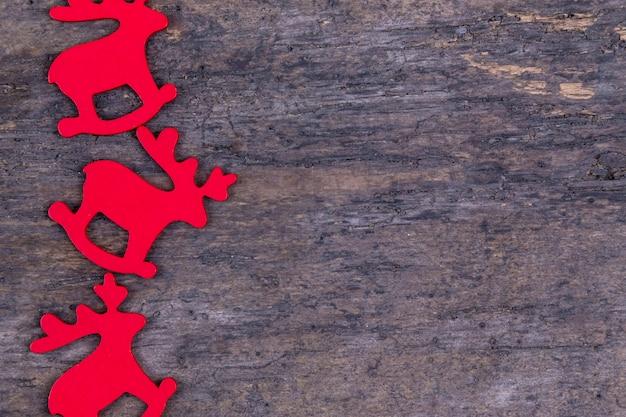 赤い鹿とクリスマスの背景は、木製おもちゃのクリスマスフレームに並んでいた。赤い鹿、木製のおもちゃで作られたクリスマスフレームとクリスマスの背景