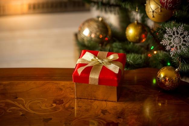 燃える暖炉とクリスマスツリーの前に木製のテーブルに赤いギフトボックスとクリスマスの背景