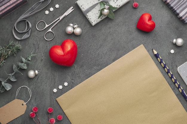 Christmas background with red stone hearts, wrapped gifts, tags, cords and trinkets on dark, copy-space.